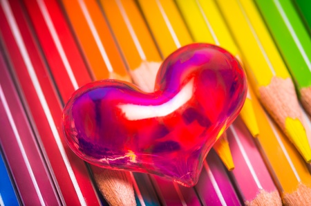 Romantic red translucent heart on a set of vibrant coloured pencils in the colours of the spectrum Stock Photo