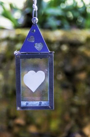 Hanging blue metal lantern with romantic heart motifs on the glass suspended outdoors against foliage