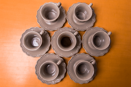 Overhead view of an arrangement of six empty pottery coffee cups and saucers around a single central one filled with espresso coffee, conceptual of individuality and a morning coffee break Stock Photo