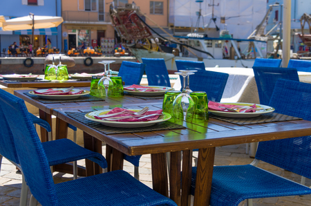 Outdoor wooden table at a restaurant set for dinner or lunch under the shade of an umbrella with urban buildings visible in the distance Stock Photo