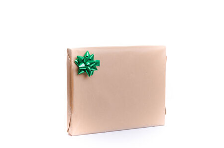 Giftwrapped present or gift box with blank wrapping and copyspace for your greeting or text with a decorative green ribbon tied in an ornamental bow, white background