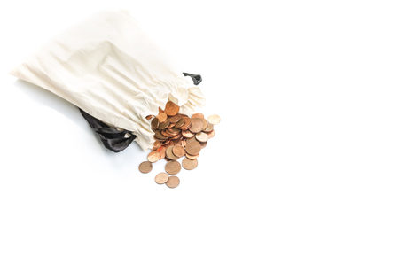 Coins and loose change spilling out of a white money bag onto a white background