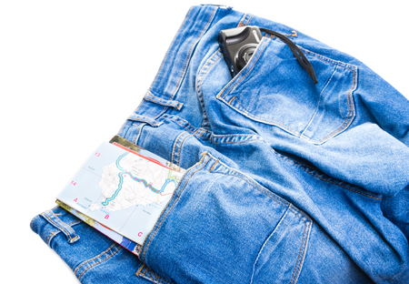 Pair of blue denim jeans with an opened letter and brochure in one back pocket and a small compact camera in the other isolated on white Stock Photo