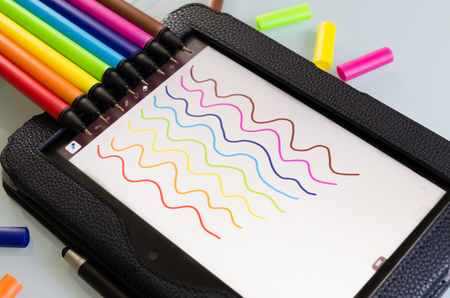 Colorful set of maker pens with squiggly lines drawn by each one on a sheet of white paper to show the vibrant color palette in the colors of the rainbow or spectrum