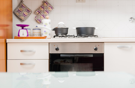 Kitchen interior with saucepans on the gas hob, a built in oven and with kitchen utensils and equipment on the counter
