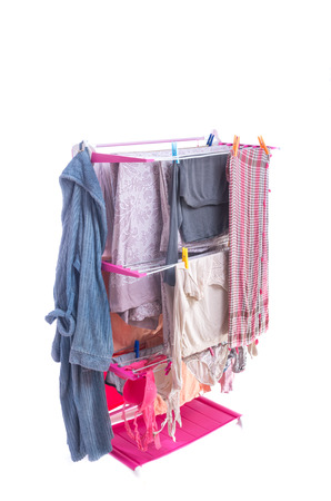 Assorted Wet Clothes Hanging on Rack Stand, Isolated on White Background. Stock Photo