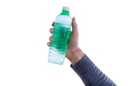 Close up of the hand of a man holding up a transparent plastic bottle of fresh water in a health and fitness concept, isolated on white