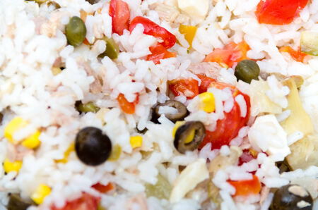 Close up background of savory cooked rice with red peppers, olives, corn, vegetables and seasoning to be served as an accompaniment to a main meal