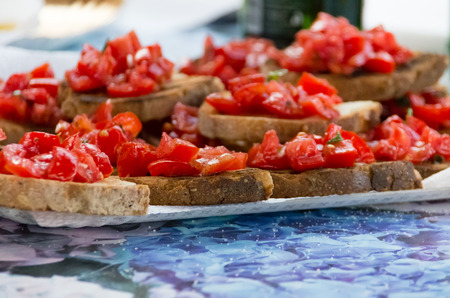 Sliced seasoned fresh tomato served on bread for finger food snacks, appetizers or canapes