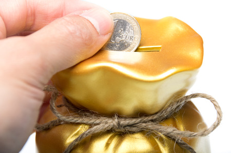 Man placing a euro coin into a gold piggy bank shaped as a money bag tied with string in a concept of savings, wealth, success and achievement