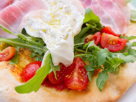 Fried egg, rocket and tomato with gourmet ham or bacon on a pita bread for a healthy snack or breakfast