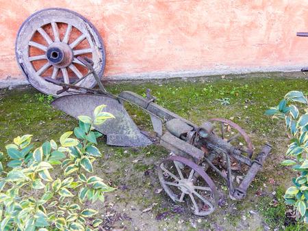 implement: Vecchia ruota del carro e attrezzo agricolo utilizzato come un display ornamentale in un cantiere di fattoria visti angolo alto sopra arbusti