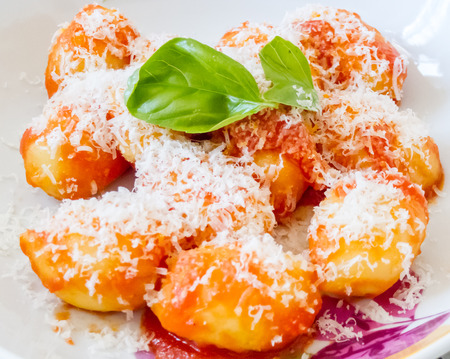 Crisp golden Italian semolina pasta and potato dumplings, or gnocci, topped with grated parmesan cheese and fresh basil