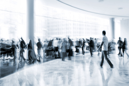 tonality: abstract image of people in the lobby of a modern business center with a blurred background and monochrome blue tonality