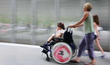 abstract image of child with disabilities in a wheelchair, accompanied and modern style with a blurred background Imagens