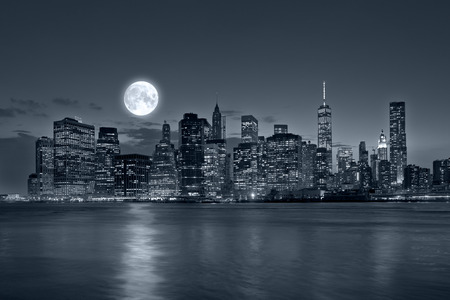Panoramic view New York City Manhattan downtown skyline at night with skyscrapers blue tonality and bright full moon Archivio Fotografico