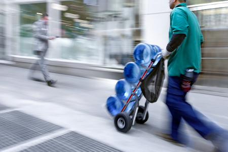purposely: delivery water with dolly by hand, purposely motion blur Stock Photo