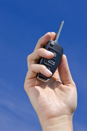 ideograph: car key in hand on blue sky background