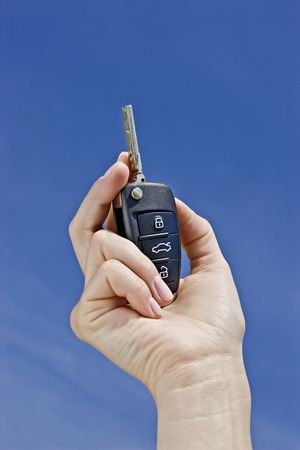 car key in hand on blue sky background