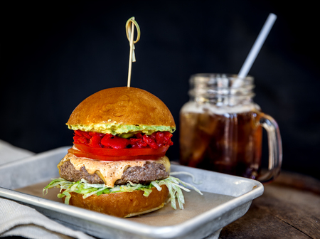 fresh and juicy hamburger with a drink on a wooden table