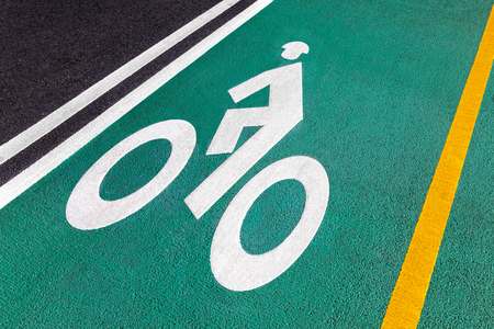 A white bike sign and a direction sign on the bike path. Reklamní fotografie