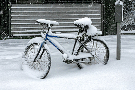 bicycle covered with snow in the winter blizzard in the parking lot Reklamní fotografie