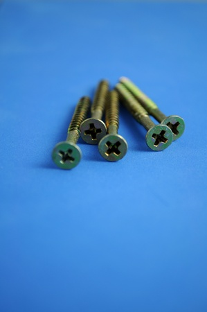screws on a blue background with intentional out of focus photo