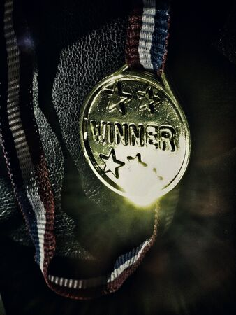 shinning light: Close view of golden medal with word winner and colorful ribbon