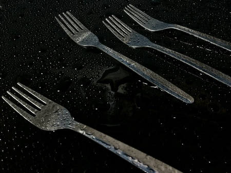silver: Close up view of forks with water drops on black background