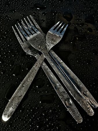 silver: Little stack of forks isolated in black background Stock Photo