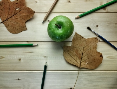 artistic: Still life with green apple and pencils Stock Photo