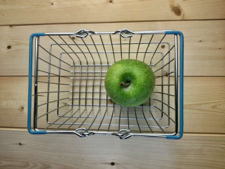 isolated: View of isolated shopping basket and green apple