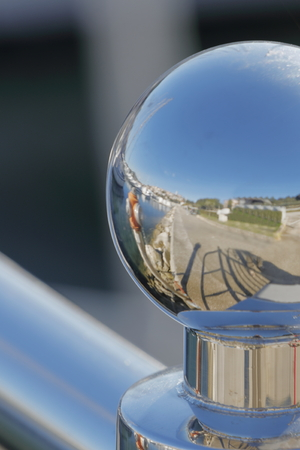 A chromed knob reflects the dock of a harbor