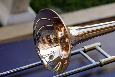 a brass-colored trumpet reflects the surrounding images