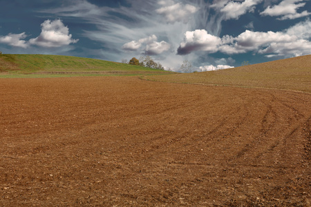 landscape at cultivated plowed field at dusk under cloudy sky 스톡 콘텐츠