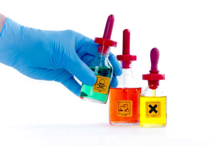 Blue gloved hand holding a chemical bottle with other chemicals labelled with irritant, flammable and toxic labels   Isolated on white  photo