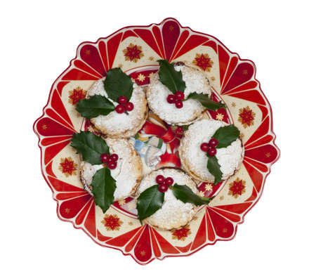 Traditional Christmas English mincepies decorated with icing sugar and holly with berries   On an attractive  old fashioned cream and red plate  Isolated on white  photo