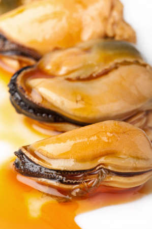 aperitive: Three mussels on a white plate with a golden brown escabeche sauce