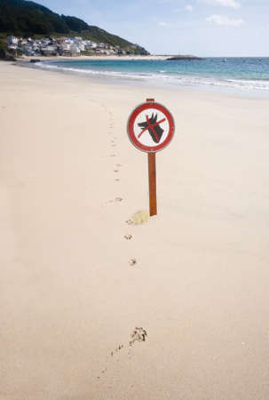 Dogs forbidden sign next to a line of dog paw prints.  The dog has urinated on the base of the sign Stock Photo - 15260143