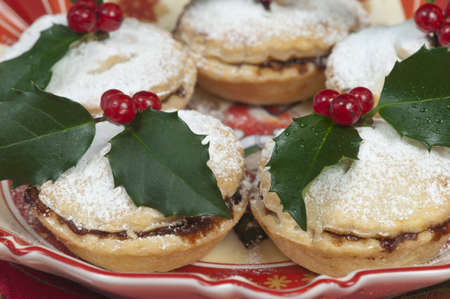 Traditional Christmas English mincepies decorated with icing sugar and holly with berries   On an attractive  old fashioned cream and red plate  Stock Photo