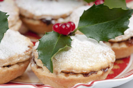 Traditional Christmas English mincepies decorated with icing sugar and holly with berries.  On an attractive  old fashioned cream and red plate.