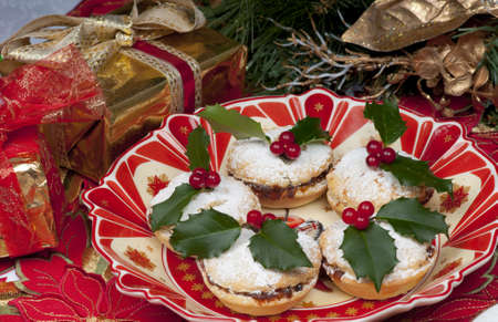 Traditional Christmas English mincepies decorated with icing sugar and holly with berries.  On an attractive  old fashioned cream and red plate. photo