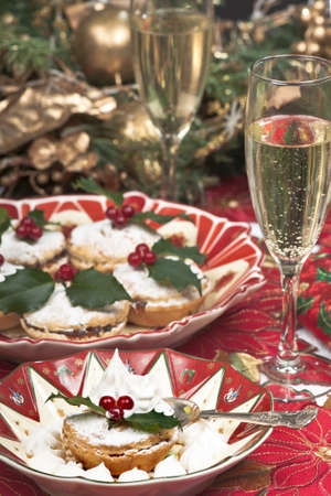 Traditional Christmas English mincepies decorated with fresh cream,icing sugar and holly with berries.  On an attractive  old fashioned cream and red plate and glasses of celebratory champagne. photo