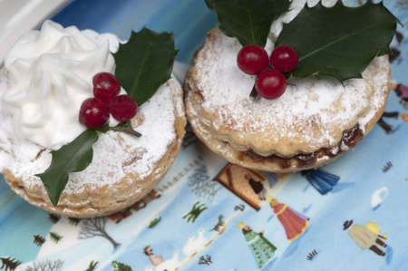 mincing: Traditional Christmas mince pies on a beautiful plate depicting a Christmas snow scene. Stock Photo