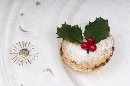 Traditional Christmas mince pie on a beautiful plate depicting the moon and sun.. Stock Photo