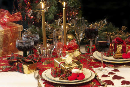 christmas dish: Traditional Christmas table setting with tree, presents, candles, lights, cracker, and red wine,