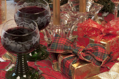banquet table: Traditional Christmas table with presents, candles, and red wine,
