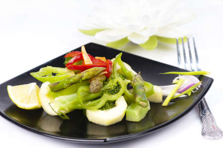 Freshly stir fried Thai  green salad with asparagus tips, cucumber, broccoli, green and red pepper, chili.  Garnished with lime and red onion dressed with a fish sauce, vinegar and brown sugar dressing.  On a black plate. Stock Photo - 15356773