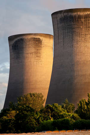 Fiddler's Ferry coal burning  station, England. Cooling towers in the evening light with trees in the foreground photo