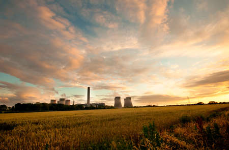carbon pollution: Dramatic view of Fiddlers Ferry coal burning power station, England. Cooling towers in the evening light with a cloudscape and field of wheat in the foreground